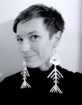 Black and white shoulders-up photo of Lara Elena Donnelly, who is smiling at the camera and wearing large earrings in the shape of fish skeletons.